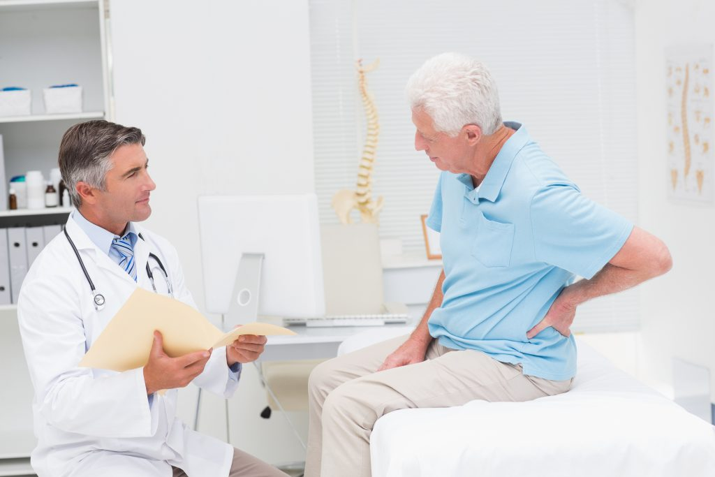 Male doctor discussing reports with senior patient suffering from back pain in clinic