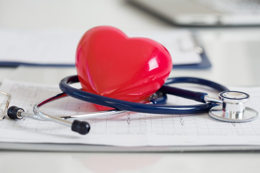 Stethescope and red heart lying on cardiogram. Healthcare cardiology and mediacal concept