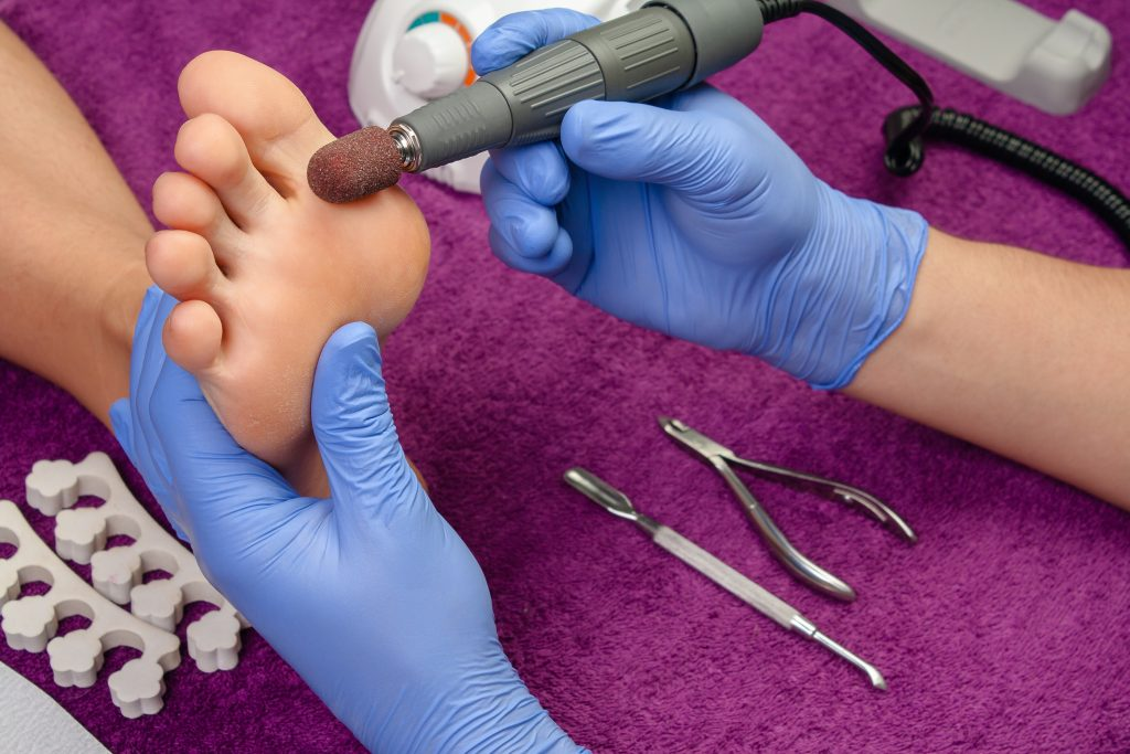 Process pedicure close-up polishing feet unrecognizable people